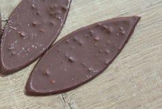 Овальный молочный шоколад с гайками на деревянной предпосылке стоковая фотография