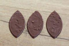 Овальный молочный шоколад с гайками на деревянной предпосылке стоковые изображения