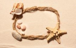 Овальная рамка веревочки, морских звёзд, seashell и камней на песке Стоковые Фотографии RF