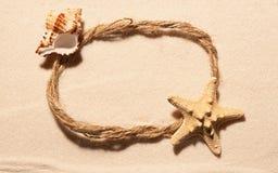 Овальная рамка веревочки с морскими звёздами и seashell на песке Стоковое Изображение