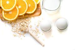 Овес шелушится плита с молоком, апельсином, яичками на деревянной белой таблице Взгляд сверху здорового овса шелушится космос экз Стоковое Фото