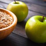 Овес шелушится в шаре и 2 яблоках Стоковое Фото