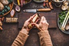 Овощи варя и есть Рука женщин женская слезая артишоки Иерусалима на темной деревенской предпосылке кухонного стола с различным Стоковые Фото