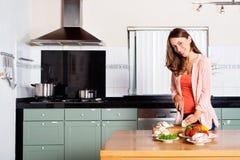 Овощи вырезывания женщины на счетчике кухни Стоковые Фото