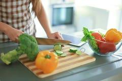 Овощи вырезывания молодой женщины в кухне дома Стоковое Изображение