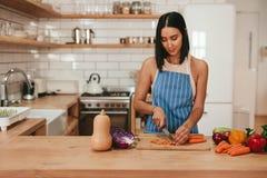 Овощи вырезывания молодой женщины в кухне дома Стоковое фото RF