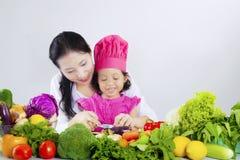 Овощи вырезывания ребенка с ее матерью стоковые фотографии rf