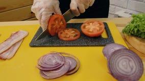 овощи вырезывания Руки женщин в перчатках целлофана с ножом отрезали свежий томат, рядом с прерванными луками сток-видео