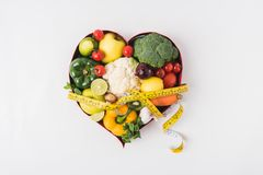 овощи и плодоовощи кладя в сформированное сердце dish около стетоскопа и измеряя ленты Стоковая Фотография