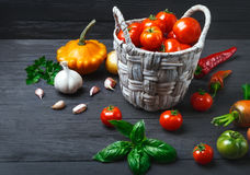 Овощи и специи в корзине на деревянном Стоковые Изображения
