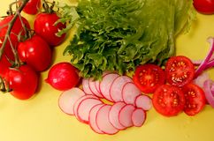 Овощи как редиска, томат и салат на желтой предпосылке стоковое изображение