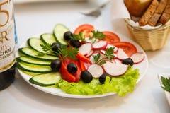 Овощи красиво отрезанные на белом блюде Огурец, красный томат, красный болгарский перец, оливки, редиска, петрушки лист ser краси стоковые изображения rf
