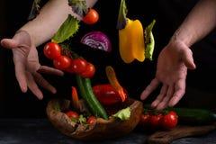 Овощи летая для салата между мужскими руками Здоровая вегетарианская еда левитация над деревянным шаром на темной каменной таблиц стоковое фото rf
