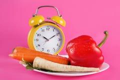 Овощи на плите и ретро будильнике изолированных на розовой предпосылке стоковая фотография