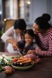 Овощи на таблице против семьи мульти-поколения подготавливая еду в кухне Стоковое Изображение