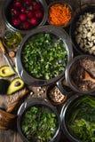 Овощи, нуты, травы в шарах в воде, половине авокадоа на таблице Стоковая Фотография
