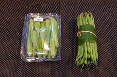 Овощ в оболочке в листьях банана против пластиковая упаковка стоковая фотография