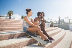 2 довольно женских друз сидя на говорить лестниц Стоковые Изображения