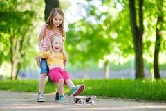 2 довольно маленьких сестры имея потеху совместно уча к скейтборду outdoors Стоковые Изображения