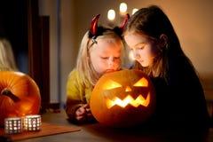 2 довольно молодых сестры в хеллоуине костюмируют высекать тыкву совместно Стоковые Фотографии RF