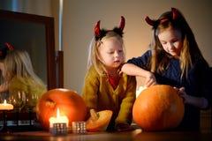 2 довольно молодых сестры в хеллоуине костюмируют высекать тыкву совместно Стоковые Изображения RF