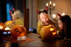 2 довольно молодых сестры в хеллоуине костюмируют высекать тыкву совместно Стоковая Фотография RF
