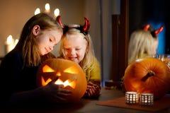 2 довольно молодых сестры в хеллоуине костюмируют высекать тыкву совместно Стоковое Изображение RF