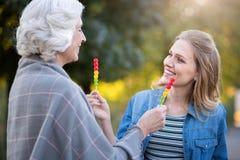 2 довольно радостных женщины показывая lollypops одина другого Стоковое Изображение RF