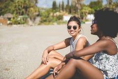 2 довольно счастливых девушки сидя на пляже Стоковые Фотографии RF