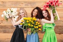 3 довольных женщины держа букеты цветков Стоковые Фотографии RF