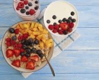 Овсяная каша, клубника, десерта голубики абрикоса поленики югурт естественного очень вкусного сладостный домодельный на голубой д Стоковые Изображения RF