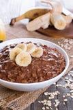 Овсяная каша шоколада для завтрака с кусками зрелого банана в белом шаре на деревянной предпосылке в горизонтальном положении Стоковые Фото