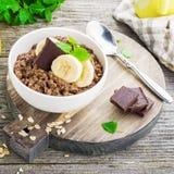 Овсяная каша шоколада для завтрака с кусками зрелого банана и частей горького хорошего шоколада в белом керамическом шаре Стоковое Изображение RF