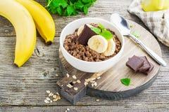 Овсяная каша шоколада для завтрака с кусками зрелого банана и частей горького хорошего шоколада в белом керамическом шаре Стоковые Фото