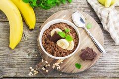 Овсяная каша шоколада для завтрака с кусками зрелого банана и частей горького хорошего шоколада в белом керамическом шаре Стоковые Изображения