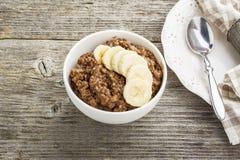 Овсяная каша шоколада для завтрака с кусками зрелого банана и частей горького хорошего шоколада в белом керамическом шаре Стоковая Фотография