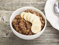 Овсяная каша шоколада для завтрака с кусками зрелого банана и частей горького хорошего шоколада в белом керамическом шаре Стоковое Изображение