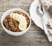 Овсяная каша шоколада для завтрака с кусками зрелого банана и частей горького хорошего шоколада в белом керамическом шаре Стоковые Фотографии RF