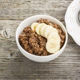 Овсяная каша шоколада для завтрака с кусками зрелого банана и частей горького хорошего шоколада в белом керамическом шаре Стоковое Фото