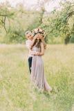 догадка которая Жизнерадостные привлекательные глаза заключения парня его венка милой девушки нося стоя в саде и ждать его Стоковая Фотография RF