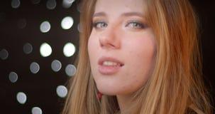 Оглушать белокурая модель с макияжем яркого блеска темным наблюдает в камеру с милой улыбкой на предпосылке bokeh видеоматериал