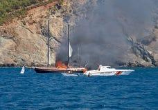 Огонь на турецкой яхте в Средиземном море Шлюпка службы береговой охраны и 2 маленькой лодки пришли к спасению Яхта все на ели стоковые фото