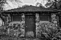 Огороженное утесом миниатюрное здание уборного стоковое фото