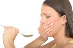 Огорченная опасливая несчастная молодая женщина держа ложку кубов белого сахара Стоковые Фотографии RF