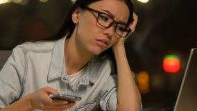 Огорченная студентка перечисляя смартфон, отсутствие намерения сделать проект сток-видео