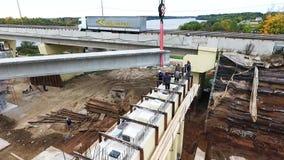 Огромная динамическая конструкция с кранами, woking мужчинами рядом с мостом над рекой видеоматериал