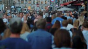 Огромная толпа людей идет на косое улицы Damrak в Амстердаме - замедленном движении - АМСТЕРДАМ/ГОЛЛАНДИЯ - 21-ое июля видеоматериал