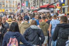 Огромная толпа туристов на известной улице Damrak в Амстердаме - АМСТЕРДАМЕ - НИДЕРЛАНДЫ - 20-ое июля 2017 стоковые фотографии rf