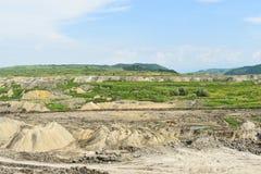 Огромная угольная шахта открытого карьера сделанная с большими экскаваторами, затяжелителями, тележками и штабелируя машинами Тяж стоковое фото rf
