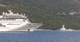 Огромное туристическое судно пассажира и небольшая частная яхта мотора с вертодромом в заливе Boka Kotorska стоковая фотография